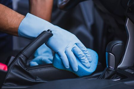 cropped view of car cleaner wiping car seat with sponge