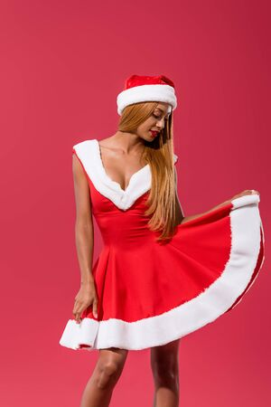 sexy african american girl in santa hat raising skirt of christmas dress isolated on red