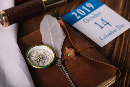 calendar with October 14 date near leather notebook with nib and compass on wooden surface 写真素材