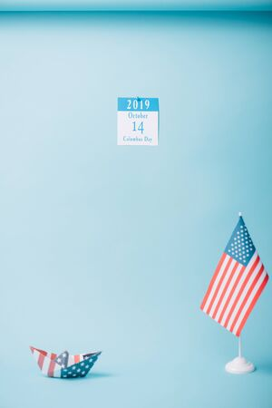 paper calendar with Columbus Day inscription near paper boat and American national flag on blue background Banque d'images - 132963732