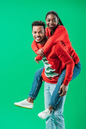 African American man holding on back woman in Christmas sweater isolated on green Stok Fotoğraf