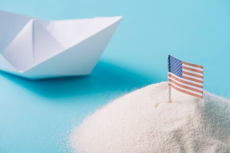 white paper boat near sand with American national flag on blue background Banque d'images - 132963350