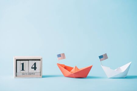 wooden calendar with October 14 date near paper boats with American flag pattern on blue background Banque d'images - 132963354