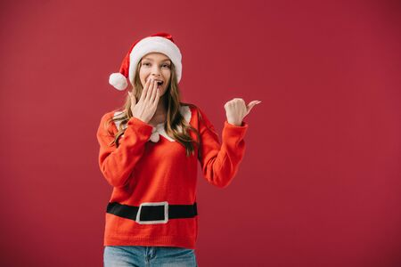 attractive woman in santa hat and sweater pointing with finger isolated on red Stock Photo