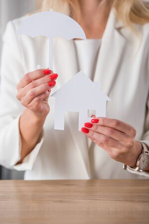 cropped view of businesswoman showing white paper cut house and umbrella