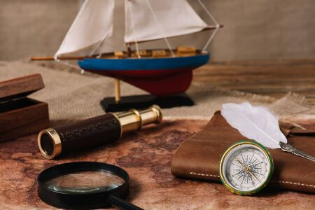 ship, telescope, magnifying glass, leather copy book and nib on old world map and hessian 写真素材
