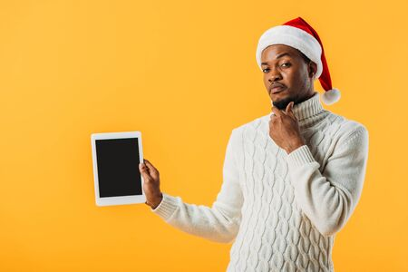 African American man in winter sweater and Santa hat holding digital tablet with blank screen and stroking chin isolated on yellow Stockfoto