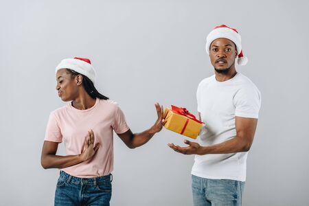 African American woman in Santa hat rejecting gift box from man isolated on grey