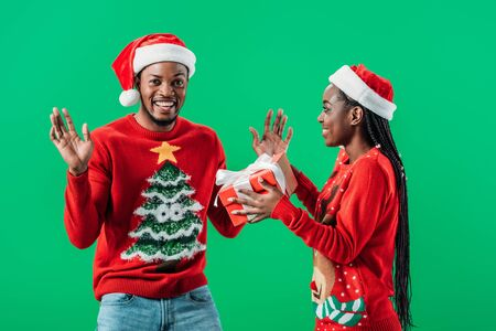 African American woman in red Christmas sweater and Santa hat giving gift box to surprised man isolated on green