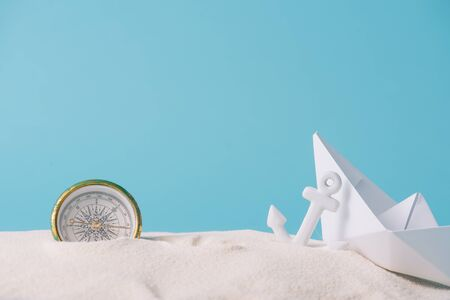 white sand with paper boat, compass and anchor isolated on blue Banque d'images - 133000599