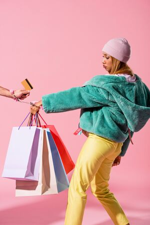 cropped view of male hand with credit card handcuffed with offended african american woman holding shopping bags on pink background, fashion doll concept Foto de archivo
