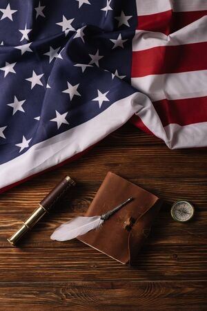 top view of leather notebook, nib, telescope and compass on wooden surface with American national flag