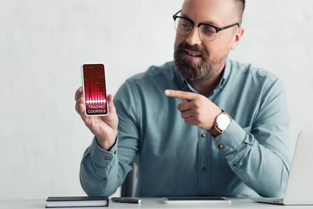 handsome businessman in shirt pointing with finger at smartphone with trading courses website
