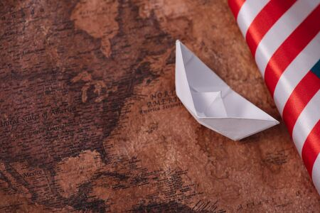 white paper boat near American national flag on ancient world map Banque d'images - 132998985