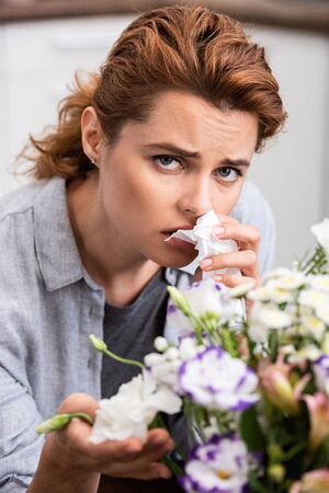 selective focus of sick woman with pollen allergy holding tissue and touching flowers Stock Photo