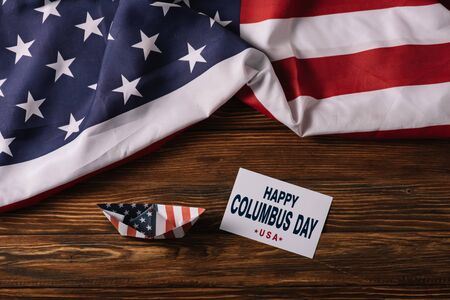 top view of card with happy Columbus Day inscription near paper boat on wooden surface with American national flag Banque d'images - 132999040