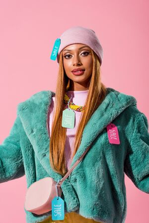 stylish african american woman with sale labels on clothes looking at camera isolated on pink, fashion doll concept