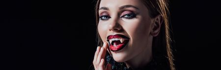 panoramic shot of scary vampire girl showing fangs in black gothic dress isolated on black