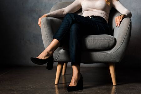 cropped view of businesswoman sitting on armchair in office Stock Photo
