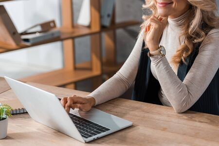 cropped view of businesswoman sitting at table and using laptop