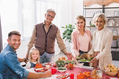 Familienmitglieder, die an Thanksgiving am Tisch sitzen und Teller mit Truthahn halten Standard-Bild