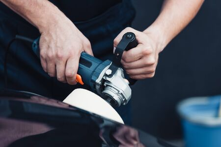partial view of car cleaner polishing black car with buffer machine