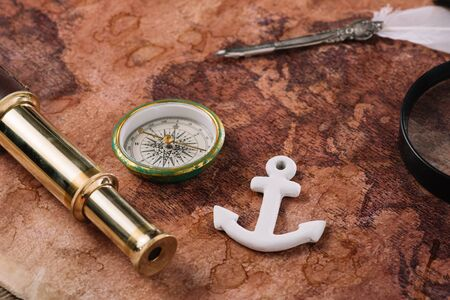 compass, white anchor, nib and telescope on world map