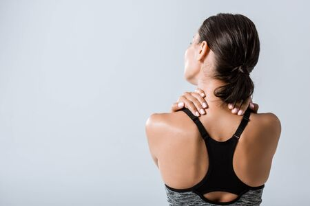 back view of sportswoman with neck pain isolated on grey