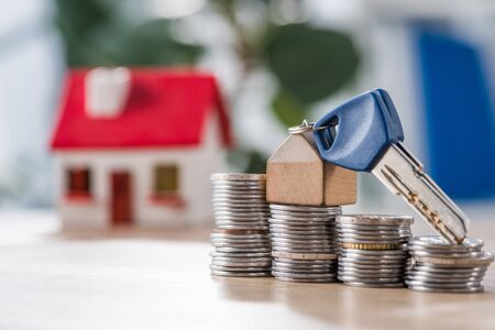 selective focus of key with toy house trinket on stacks of coins near house model on wooden table