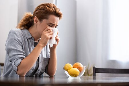 woman with runny nose sneezing in tissue near orange and lemons in bowl