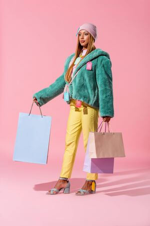beautiful, stylish african american woman holding shopping bags on pink background, fashion doll concept
