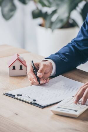 cropped view of businessman using calculator and writing in contract near house model Stock Photo