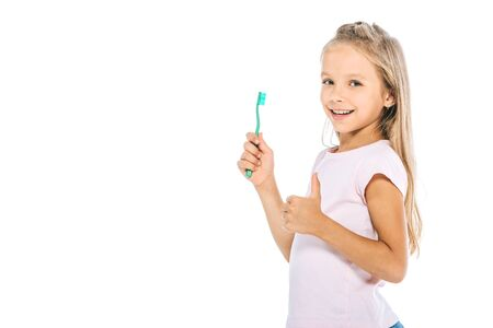happy kid holding toothbrush and showing thumb up isolated on white
