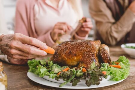 cropped view of woman putting carrot to plate with tasty turkey in Thanksgiving day   Standard-Bild