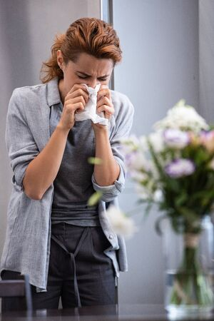 selective focus of woman sneezing in tissue near flowers in vase