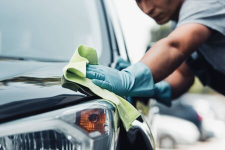 selective focus of car cleaner wiping capote with rag