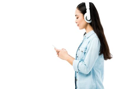 side view of attractive asian woman in denim shirt listening music and holding smartphone isolated on white