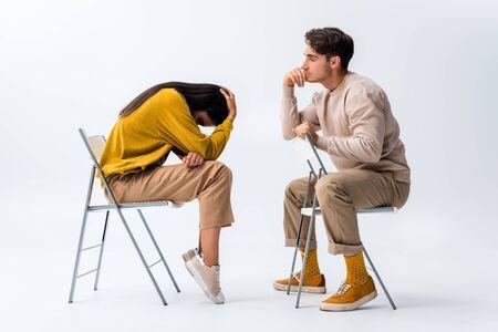Hombre sentado en una silla y mirando a la mujer molesta que cubre el rostro en blanco Foto de archivo
