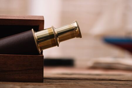 brown and golden telescope in open wooden box