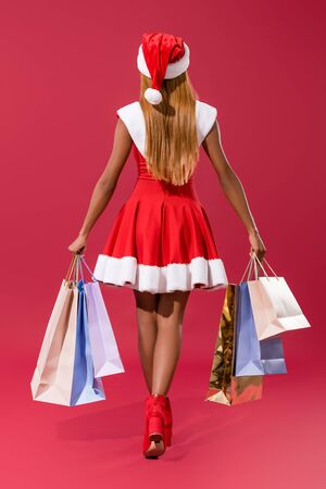 back view of young african american girl in santa hat and christmas dress walking with shopping bags on red background