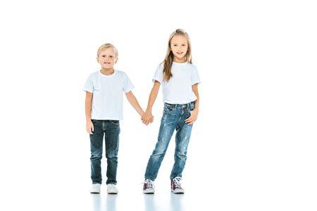 Niños lindos tomados de la mano y de pie en blue jeans en blanco