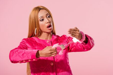 shocked african american woman looking at handcuffed hand isolated on pink, fashion doll concept Archivio Fotografico