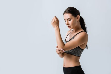 attractive sportswoman with elbow pain isolated on grey