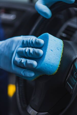 cropped view of car cleaner wiping steering wheel with sponge Foto de archivo - 132974274