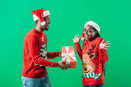 African American man in red Christmas sweater and Santa hat giving gift box to surprised woman isolated on green
