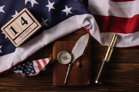 top view of wooden calendar with October 14 date, paper boat, nib, compass, telescope and leather notebook on wooden surface with American national flag
