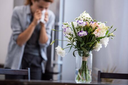 selective focus of flowers in vase near woman sneezing in tissue