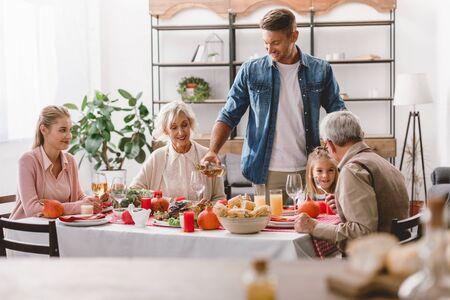 Familienmitglieder sitzen am Tisch und lächelnder Vater schenkt Wein am Thanksgiving-Tag ein?