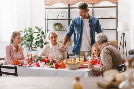 family members sitting at table and smiling father pouring wine in Thanksgiving day