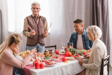 family members sitting at table and grandfather holding cutlery in Thanksgiving day